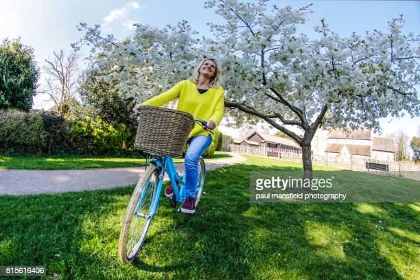 Lady riding bicyclepast a blossom tree