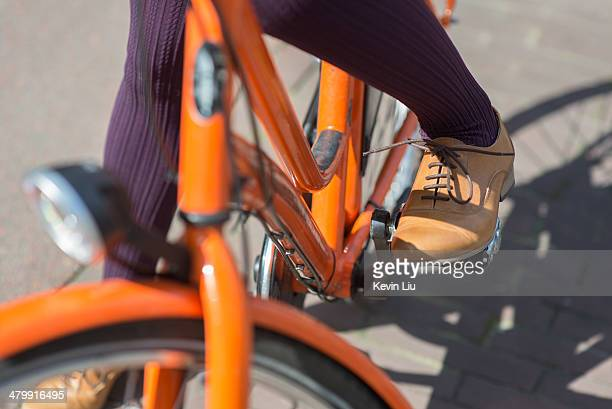 lady riding orange bike in leather shoes - orange shoe stock photos and pictures