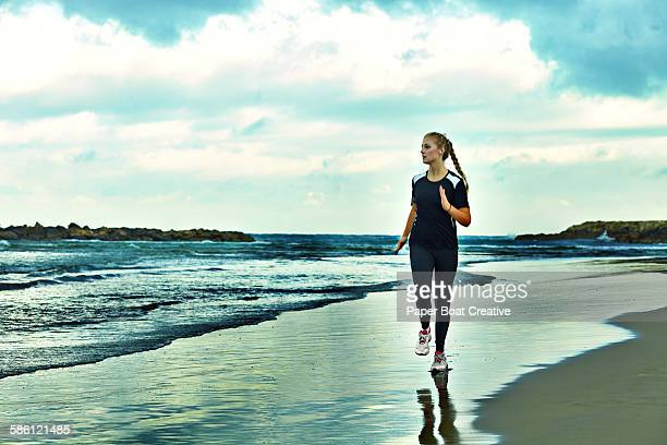 Lady running by the beach side on a cold day