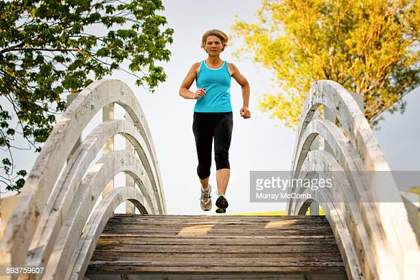 lady running over scenic footbridge - murray mccomb stock pictures, royalty-free photos & images
