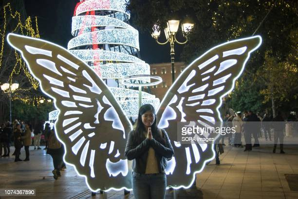 A lady seen standing front of butterfly wings at the Syntagma Square in Athens