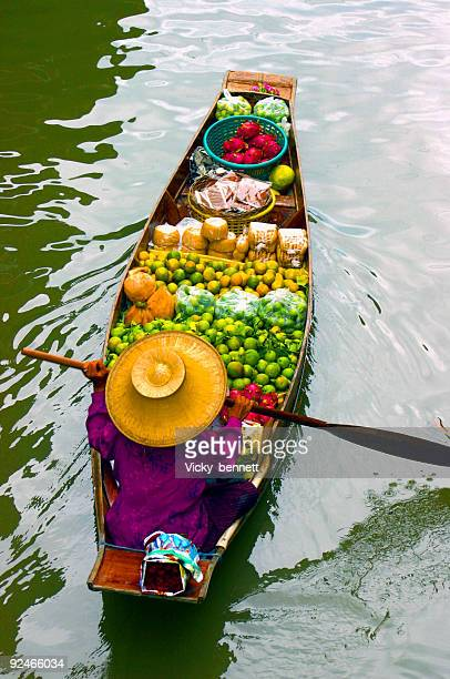 lady selling fruit from her boat at floating market, thailand - bangkok stock photos and pictures