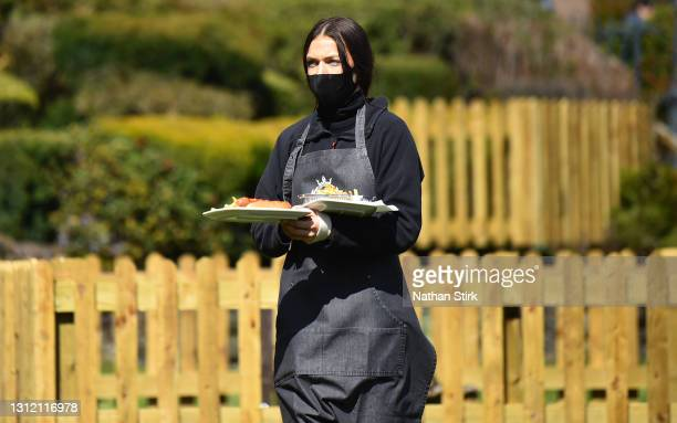 Lady serves food whilst in a beer garden at Hotel Rudyard on April 12, 2021 in Leek, England. England has taken a significant step in easing its...