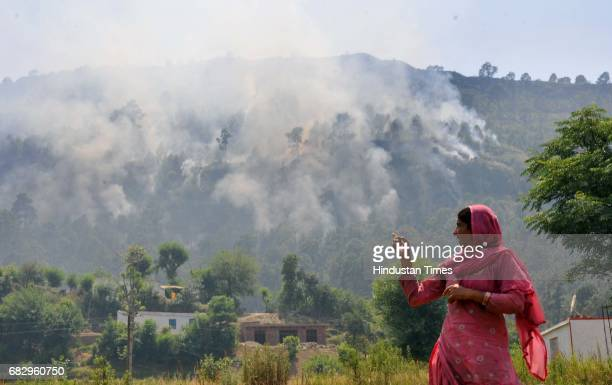 A lady showing smoke rises by mortar shells allegedly fired from the Pakistan side of the border at Jhanghar village in Nowshera on May 14 2017 in...