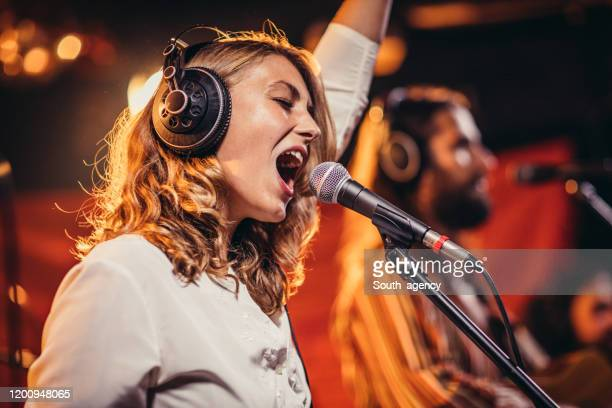 lady singing on stage with band - singer stock pictures, royalty-free photos & images