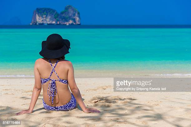 lady sits back on the beach and look at the beautiful sea and island - copyright by siripong kaewla iad stock photos and pictures