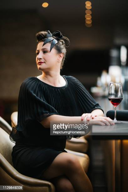 Eine Dame, die an der Theke sitzt, schaut elegant weg.