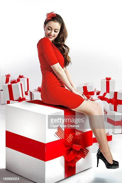 Lady sitting on a giant gift box with red ribbon