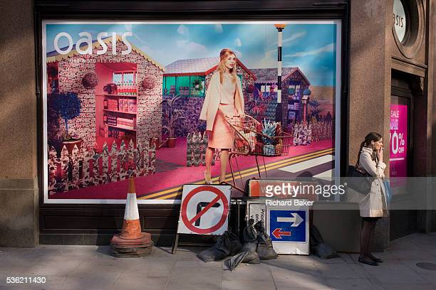 Lady smoker and roadworks signs below an Oasis fashion poster featuring a young woman in a utopian fantasy about to cross a road Stopping for a smoke...