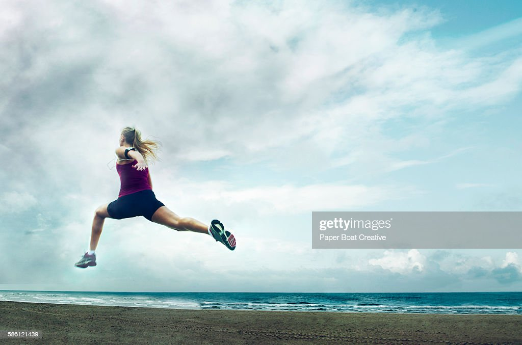 lady springing fast by the beach side during storm : Stock Photo