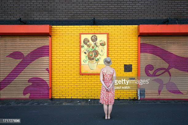 Lady standing and looking at a painting of Van Gogs sun flowers. Birmingham, England. Flowered dress.