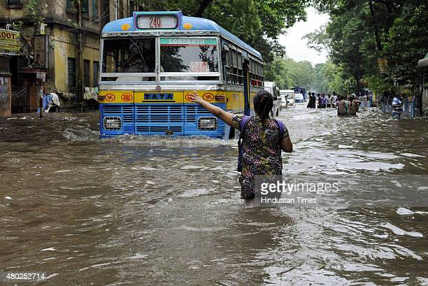 A lady standing in 2 feet deep water signals a bus to stop on water logged road at Amherst Street on July 10 2015 in Kolkata India A heavy rainfall...
