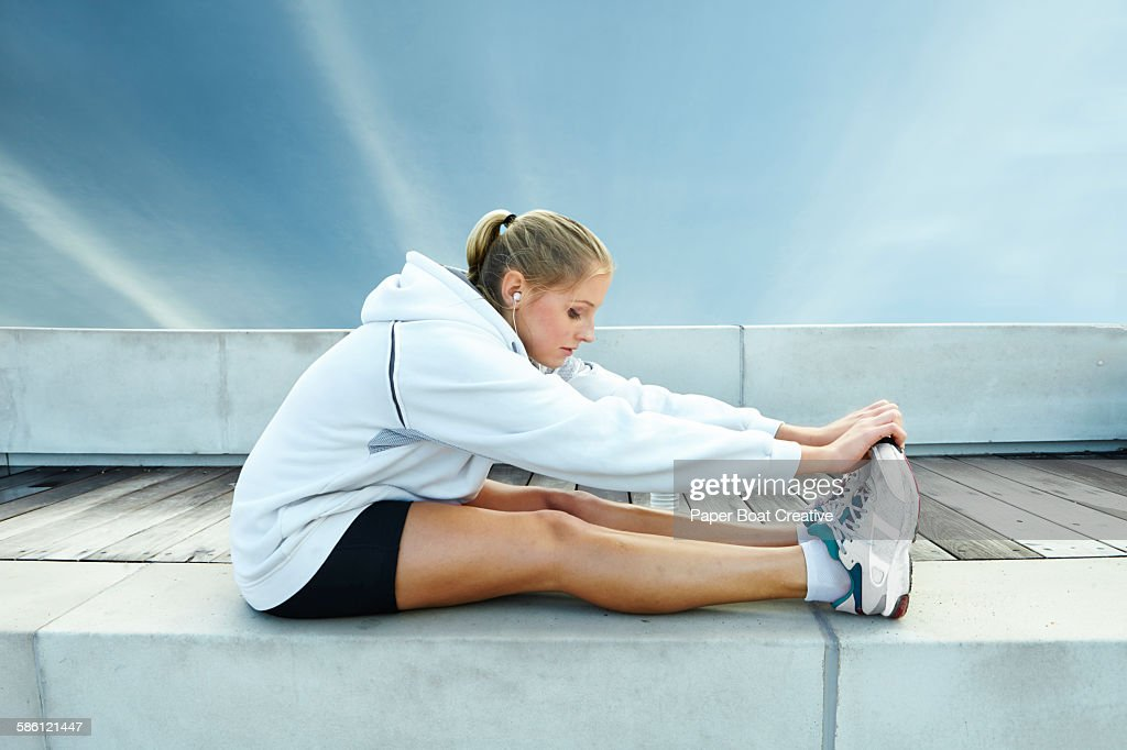 lady stretching her legs and listening to music : Stock Photo