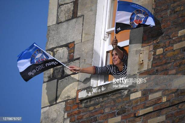 A lady supports Bath from her window at a house overlooking the pitch during the Gallagher Premiership Rugby match between Bath Rugby and Gloucester...