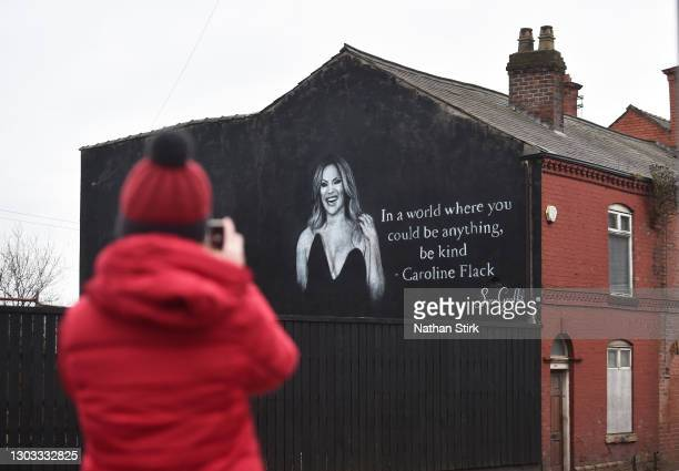 Lady takes a photo of a mural by Artists Scott Wilcock which pays tribute to TV star Caroline Flack on February 21, 2021 in Wigan, England. Ms Flack,...