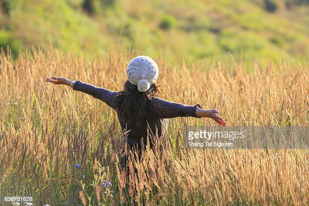 Lady traveler with camera push hands and breathing at field of grasses and forest