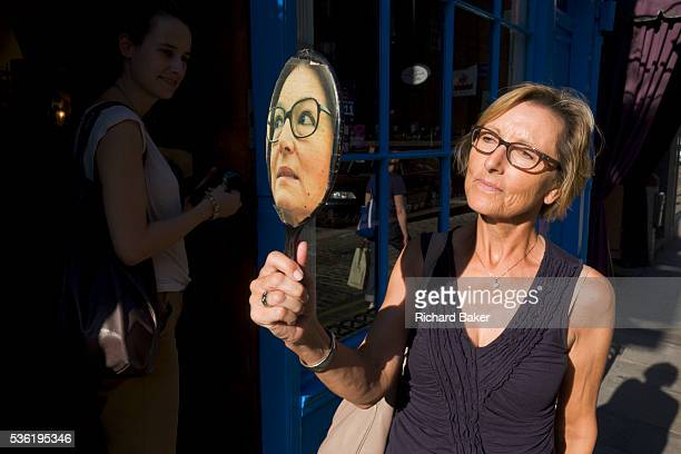 A lady tries on a pair of spectacles using a faced mirror outside a London optician In afternoon sunshine she looks into the mirror to decide whether...
