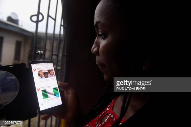 Lady tries to tweet with a smartphone in Lagos, on October 29, 2018. - Nigeria has an unenviable reputation around the world for corruption and is...