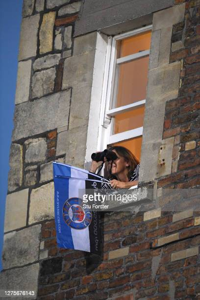 A lady uses binoculars to view the action as she supports Bath from her window at a house overlooking the pitch during the Gallagher Premiership...