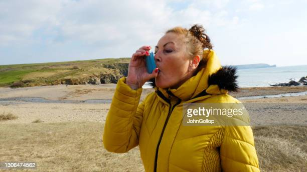 lady using an inhaler - one senior woman only stock pictures, royalty-free photos & images