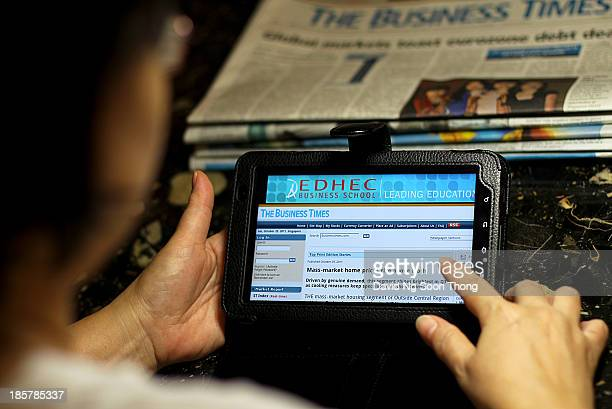 Lady using the smart Tablet to access an online e-paper for the latest business news update at home. Singapore. January 24, 2013.