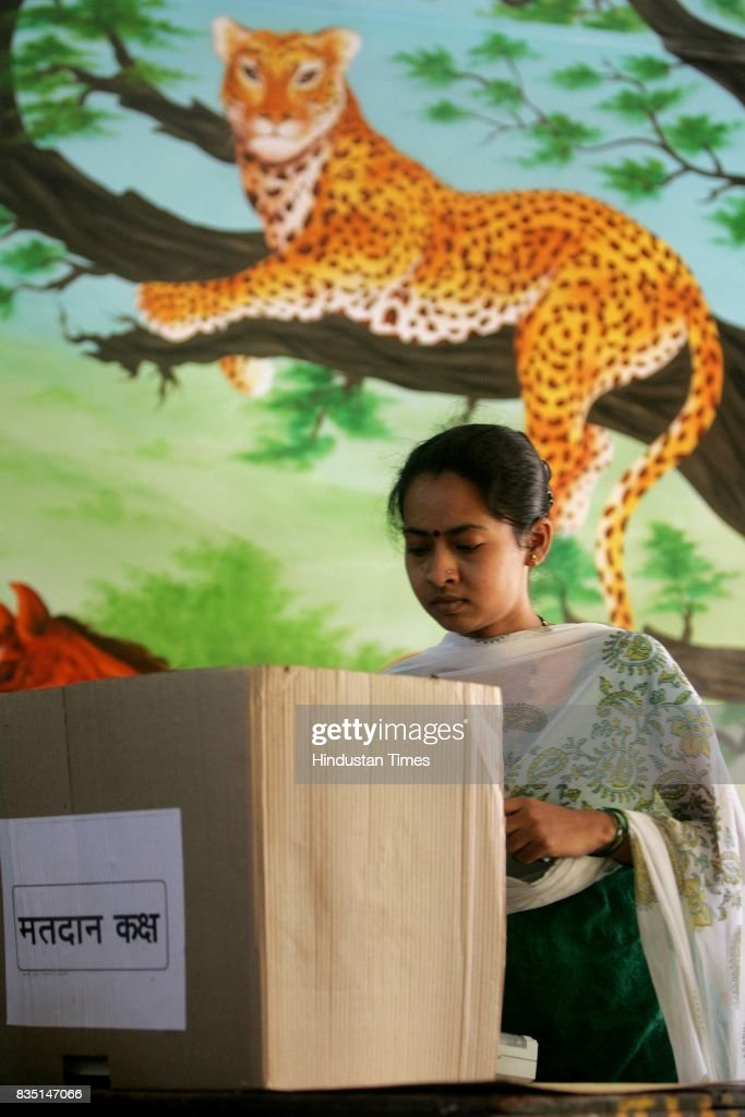 A lady voter casts her ballot under watchful eyes for the BMC elections in Malad Kurar Village on Thursday.