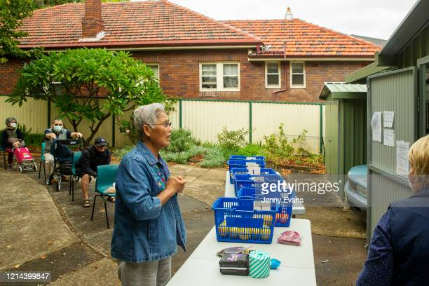 A lady waits for food at St Paul's Anglican Church in Burwood on March 24 2020 in Sydney Australia The Parish Pantry provides food for the vulnerable...