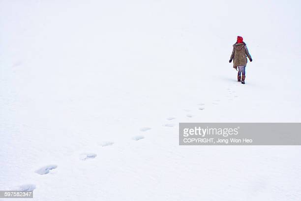 A lady walking on the white snowfield