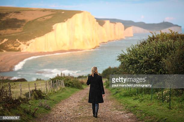 Lady walking towards cliff coastline