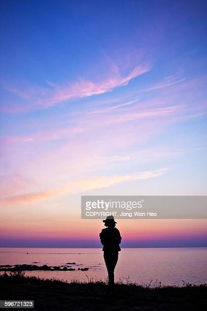 A lady walking under the sunset