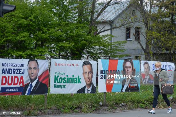 Lady walks by election banners with images of candidates Andrzej Duda, Wladyslaw Kosciniak-Kamysz, Malgorzata Kidawa and Krzysztof Bosak, seen...