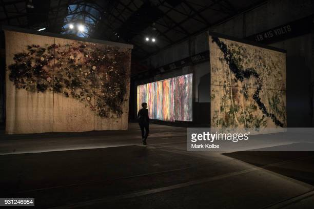 A lady walks by 'The River' by artist Sam Falls which is part of the 31st Biennale of Sydney at Carriage Works on March 13 2018 in Sydney Australia
