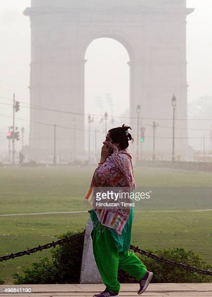 A lady walks during a smoggy morning after Diwali celebrations at India Gate on November 12 2015 in New Delhi India Air quality in the Capital...