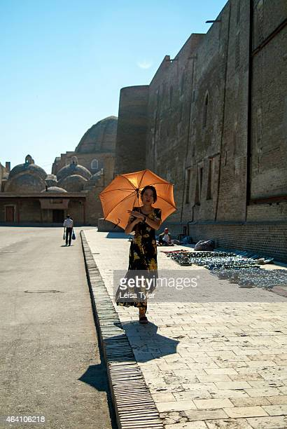 A lady walks outside the city walls of Bukhara Built in the6th century Bukhara's center is a living museum with about 140 architectural monuments...