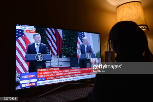 A lady watches a televised press conference from the White House with Polish President Andrzej Duda and US President Donald Trump on TVP Info On June...