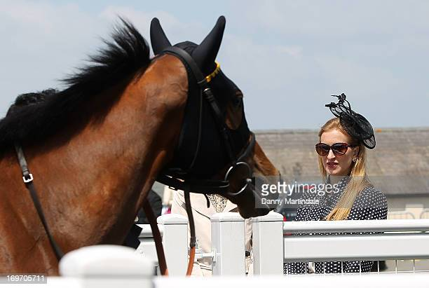 A lady watches the horses walk by on Ladies Day at the Derby Festival at Epsom Racecourse on May 31 2013 in Epsom England