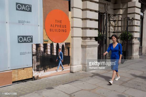 A lady wearing a distinctive blue dress walks past a board showing a man wearing a similar colour shade at the Alpheus Building on Blomfield Street a...