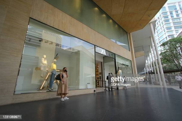 """Lady wearing a face mask stands outside a Zara Store at Antara Fashion Hall. As part of the """"Activate without Risking"""" program, Shopping Malls and..."""