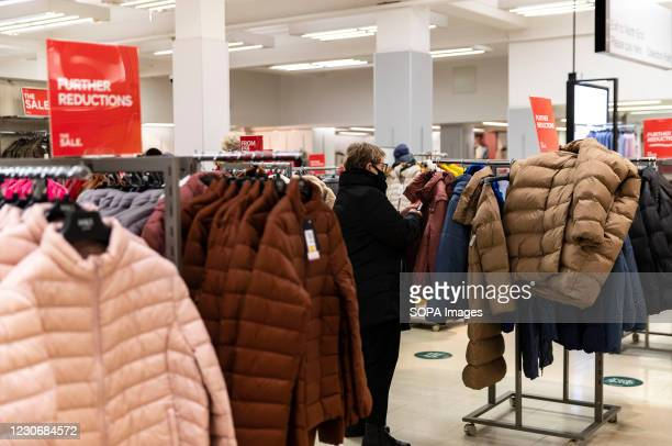 Lady wearing a facemask seen checking clothes inside Marks & Spencer, a multinational retailer specialises in selling clothing, home products and...