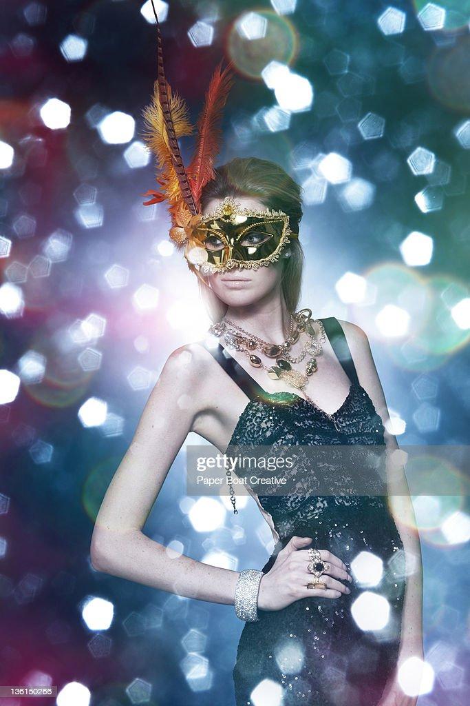 lady wearing a golden feather mask in a party : Stock Photo