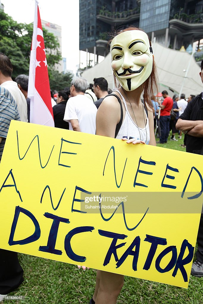 A lady wearing a Guy Fawkes mask, holds up a placard during a protest against the government's White Paper on Population and labour-related matters that affect Singaporeans at Speakers' Corner in Hong Lim Park on May 1, 2013 in Singapore. Thousands of protesters gathered today in an inaugural labour day protest against the 6.9 million population government white paper that revealed it could increase 30% to 6.9 million by 2030, angering residents who already see a strain on housing, transportation and healthcare. This is a follow up protest after one was held on 16 Feb, 2013 organised by the same organiser, transitioning.org
