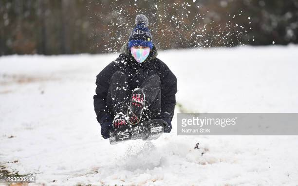 Lady wearing a mask rides a sledges down a hill in on December 29, 2020 in Newcastle-Under-Lyme, England. Heavy snow fall has covered the West...