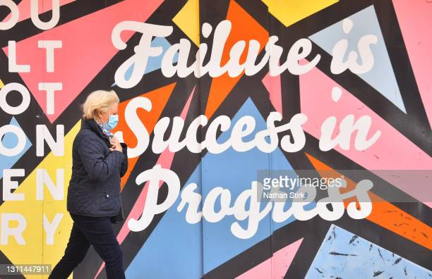 Lady wearing a mask walks past artwork saying 'Failure is success in progress' on April 08, 2021 in Stoke-on-Trent,England .