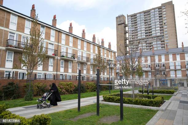 A lady wearing a niqab and pushing a pram walks while looking at her mobile phone on 27th April 2016 near Balfron Tower in East London United Kingdom...