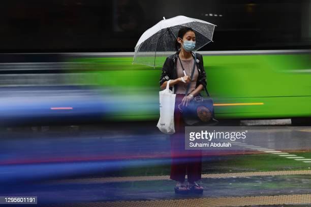 Lady wearing a protective mask waits to cross a street in the rain on January 10, 2021 in Singapore. As of January 10, the Ministry of Health...