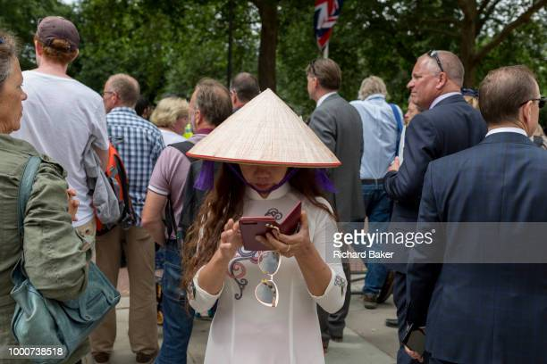 A lady wearing an Asian conical hat uses a phone to text a message during the 100th anniversary of the Royal Air Force on 10th July 2018 in London...