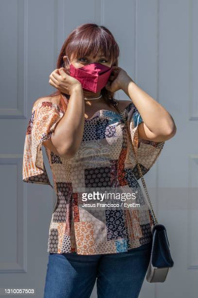 lady wearing mask from her bag to protect herself from the epidemic - laughing jesus images stock pictures, royalty-free photos & images