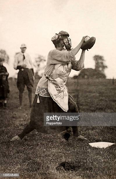 A lady wearing protective gear a catcher's glove and mask engaged in a baseball or softball game at Brize Norton USAF base near Chipping Norton in...