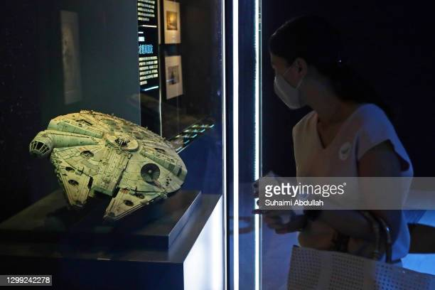 Lady wearing protective mask looks at a Millenium Falcon starship at The Star Wars Identities exhibition during a media preview at The ArtScience...