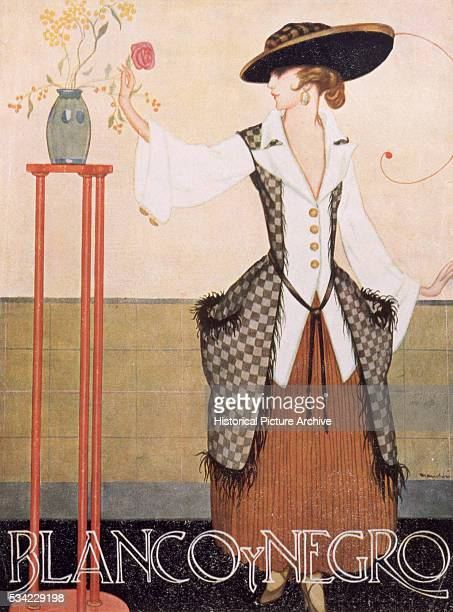 A lady wears a long checked waistcoat over a loose 'V' neck shirt and a full anklelength skirt in an illustration from the Spanish Blanco y Negro...